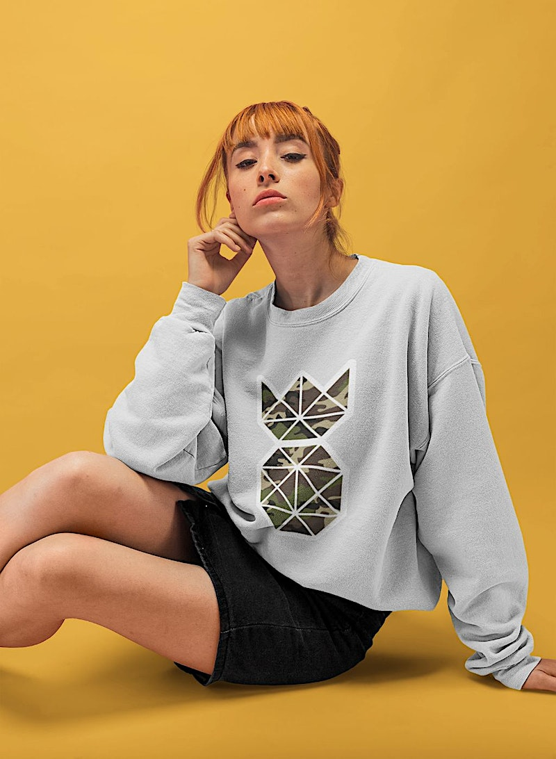 baggy sweatshirt in grey with a camouflage pineapple design of a girl with red hair bangs sitting seductively in a studio