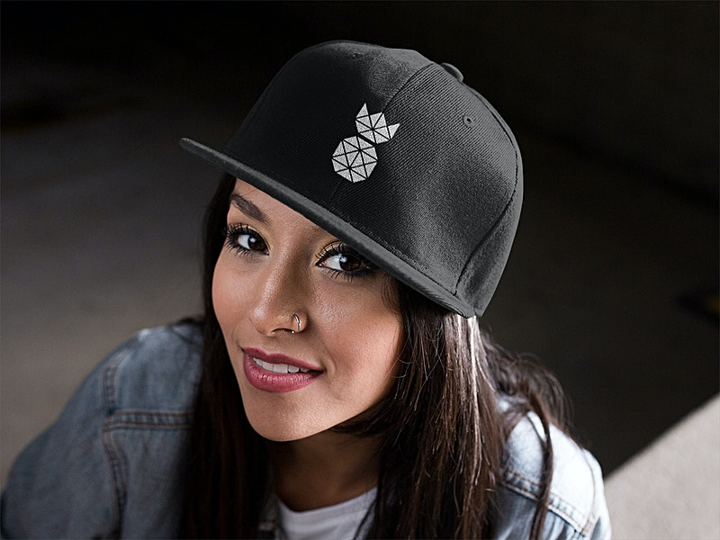 classic pineapple snapback hat in black with white embroidered pineapplesupplyco logo mockup featuring a young hispanic girl smiling