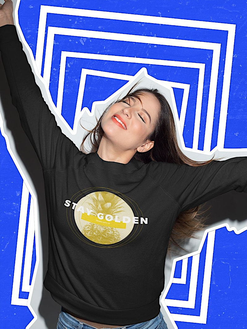 happy woman wearing a graphic crewneck sweatshirt from pineapple supply co. clothing