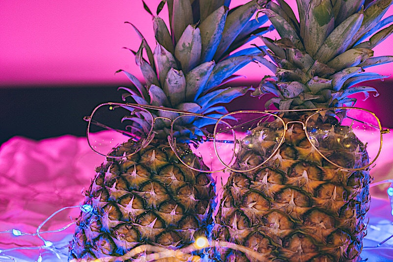 Two pineapples wearing gold glasses in neon string/fairy lights