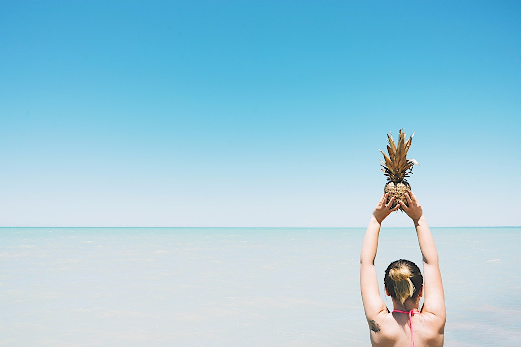Golden pineapple held up in the air as a reminder to Stay Golden