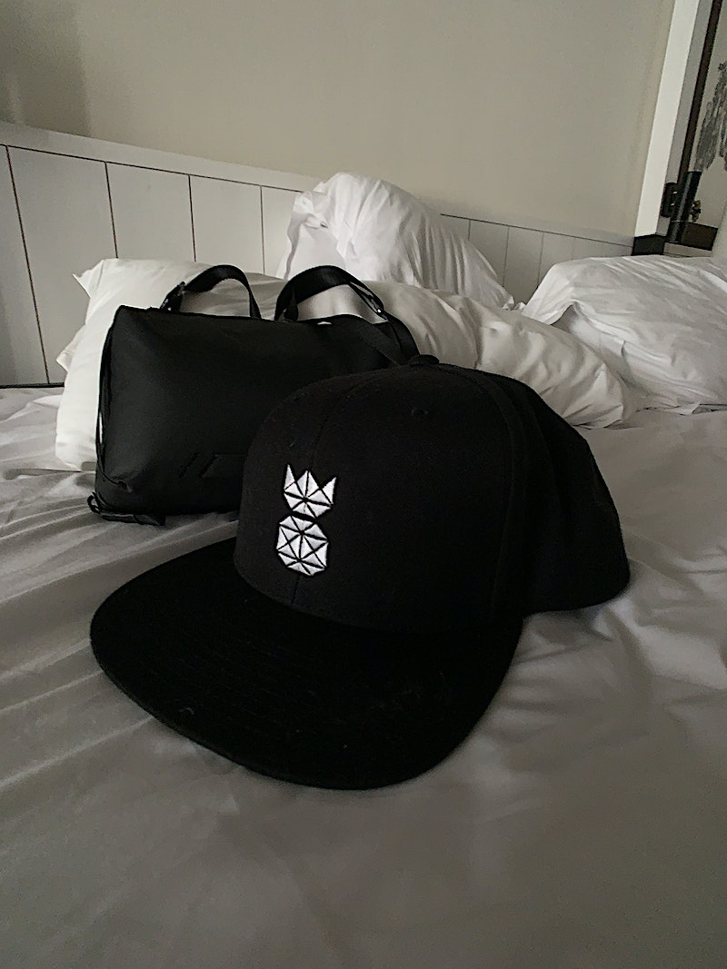 pineapple supply co snapback hat on bed