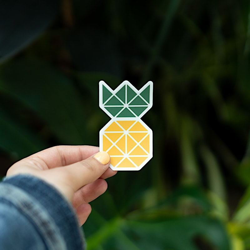 """Girl holding 3"""" size original pineapple sticker of our logo comparing it with the pineapple emoji"""
