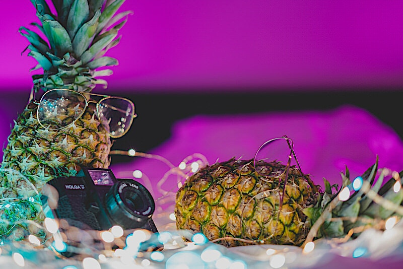 Pineapples doing a photoshoot in neon lights and fairy lights