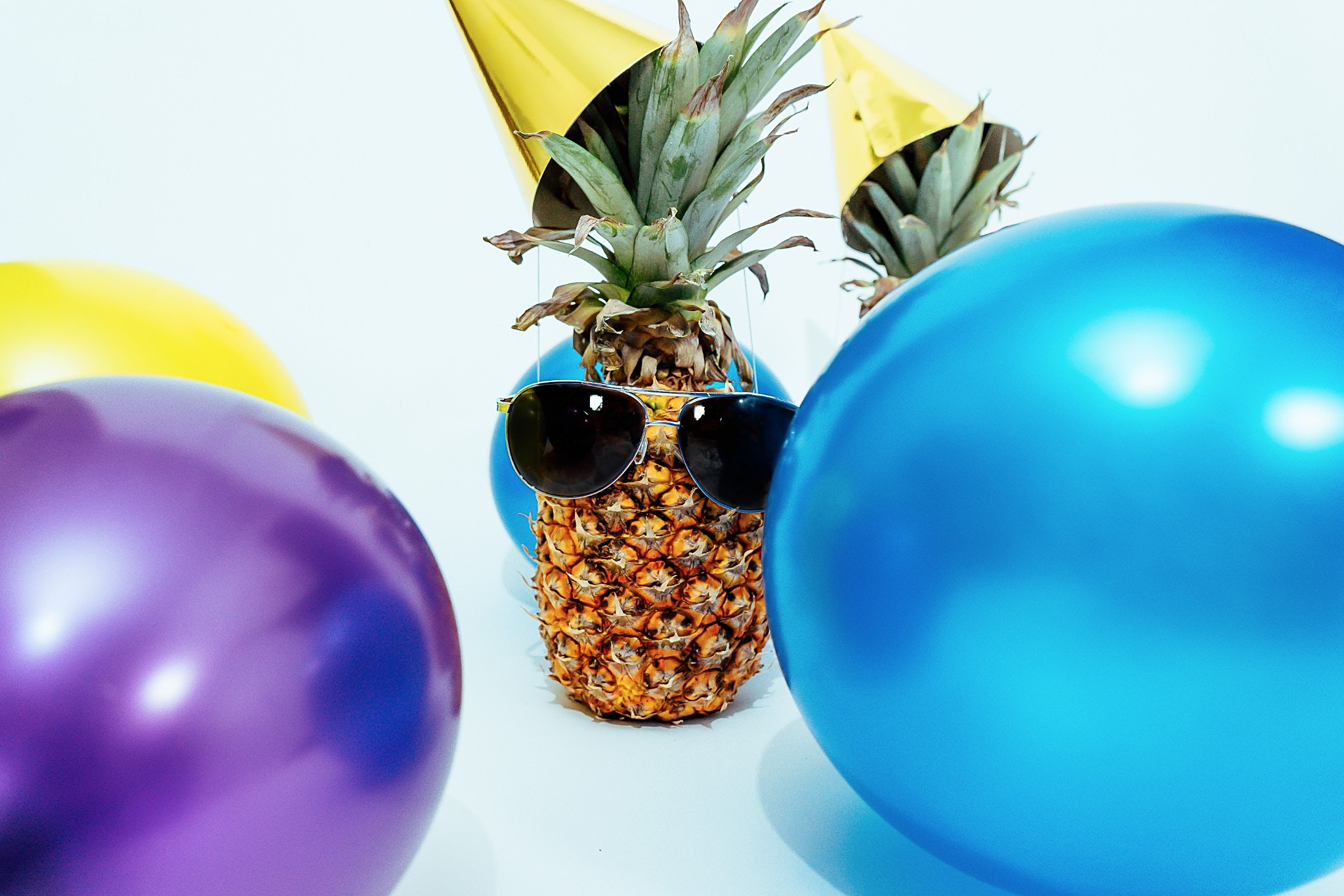 A pineapple with balloons