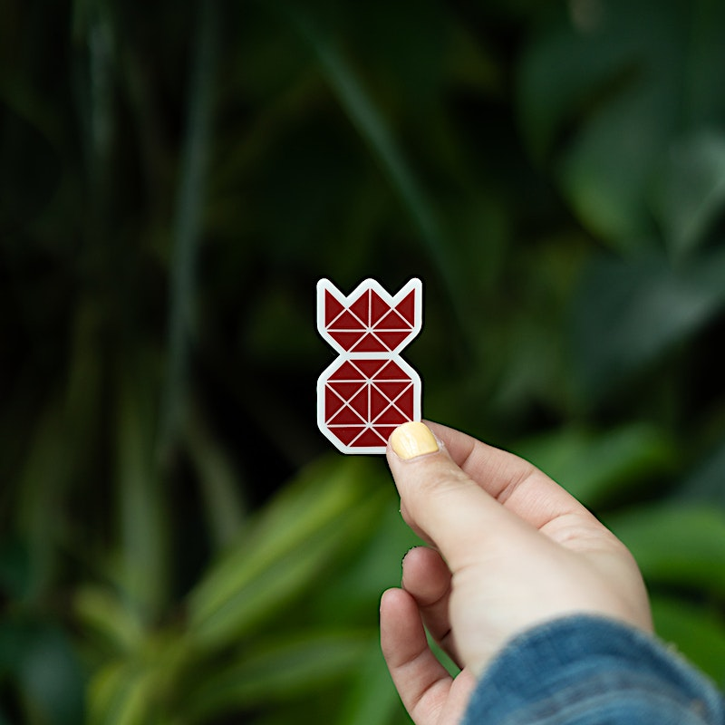 Girl holding out a Red Pineapple Sticker